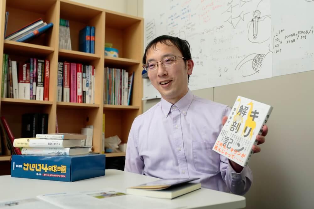 宮道和成博士が本「キリン解剖記」を手にとっている画像