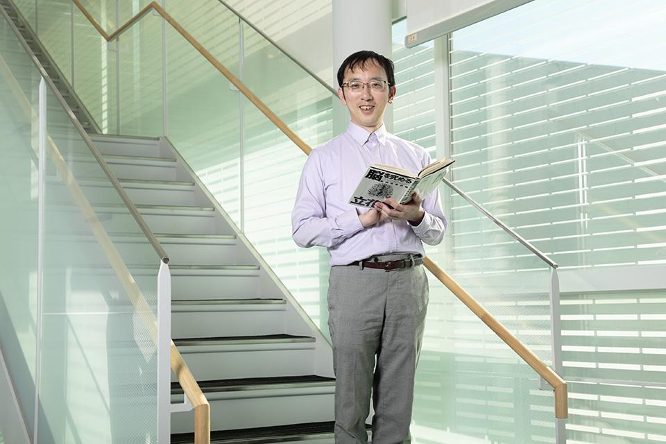 宮道和成博士が本を持って微笑んでいる画像